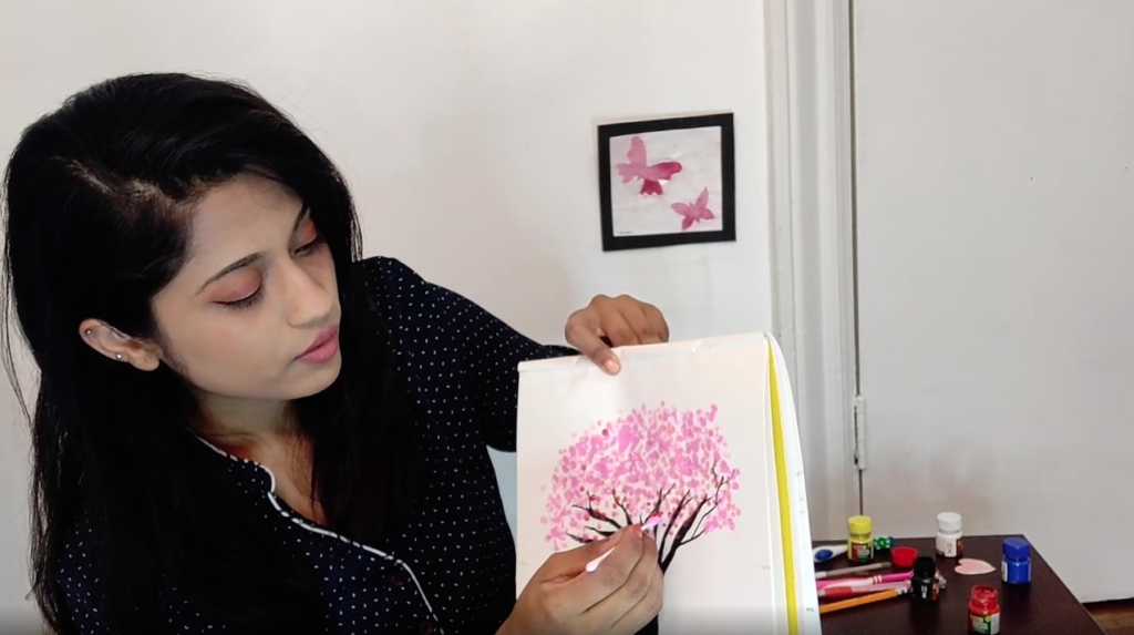 Gooroo Sam paints using a cotton swab in her painting with unconventional methods course